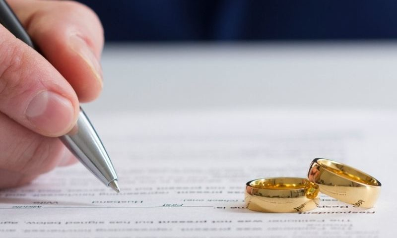 person signing papers with wedding rings